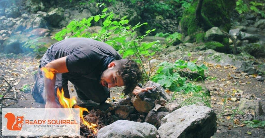 man staring camp fire