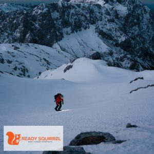 Man climbing snow covered mountain in the dark